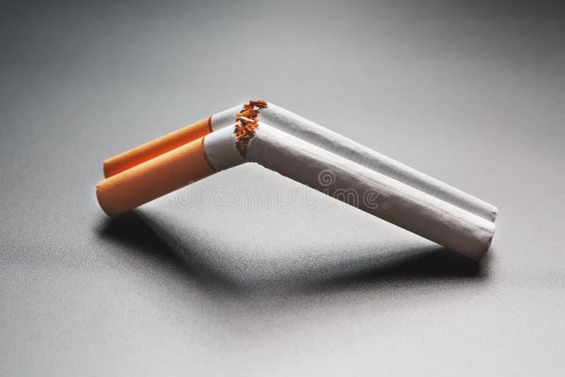Deux cigarettes sous forme de fusil de chasse ? deux coups sur un fond noir avec l'espace de copie Cessez le fumage Le concept de photos stock