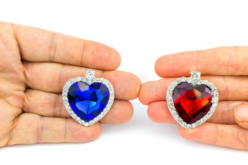 Deux coeurs de bijoux en main de l'homme et de femme photo stock