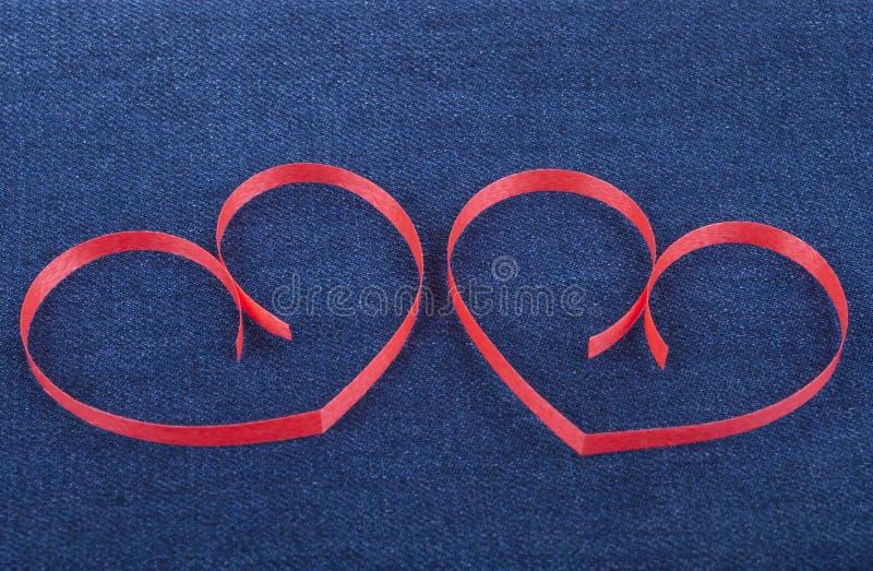 Deux coeurs de papier sur des jeans photos libres de droits