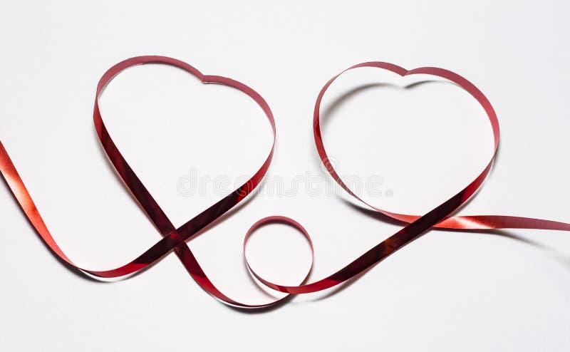 Deux coeurs de ruban rouge sur le fond blanc photo libre de droits