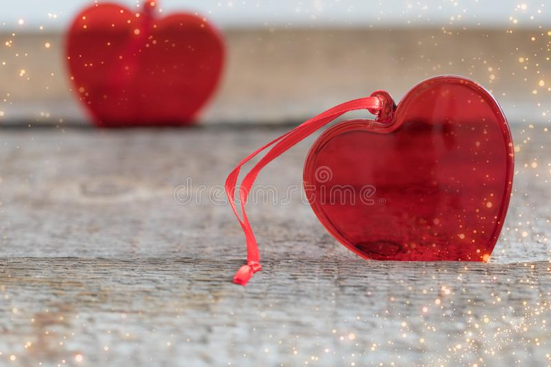 Deux coeurs en verre rouges sur le fond en bois, avec le scintillement texturisé, carte postale de jour de valentines de St images stock