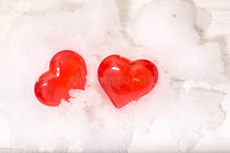 Deux coeurs en verre sur la neige image stock