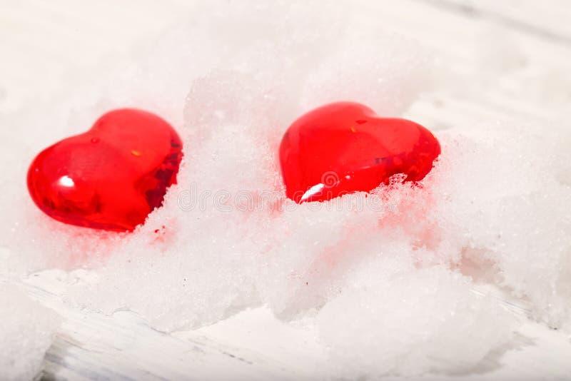 Deux coeurs en verre sur la neige photo stock