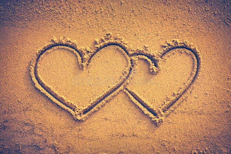 Deux coeurs manuscrits sur le sable de bord de la mer Vignette et vintage à images stock