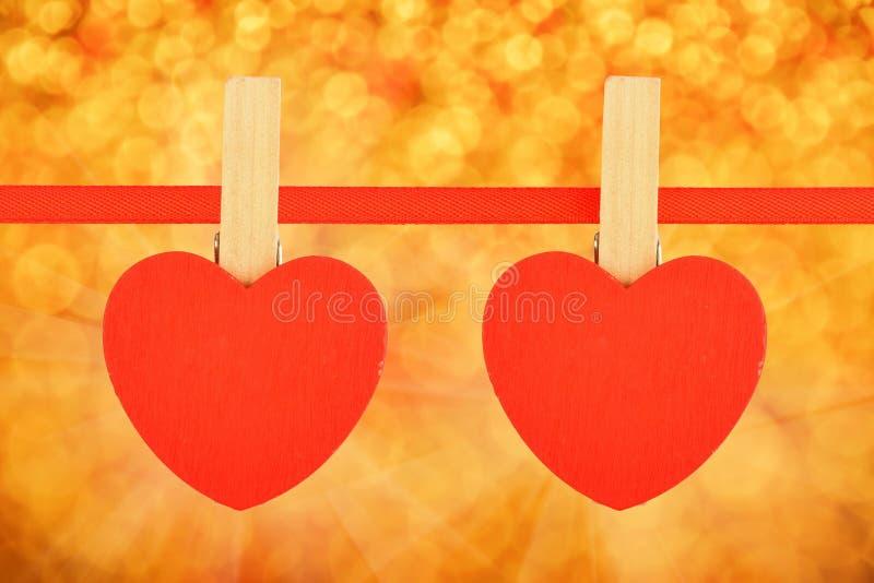 Deux coeurs rouges au ruban au-dessus de la tache floue d'or de scintillement photos libres de droits