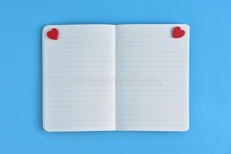 Deux coeurs rouges avec les pages vides ouvertes du carnet images stock