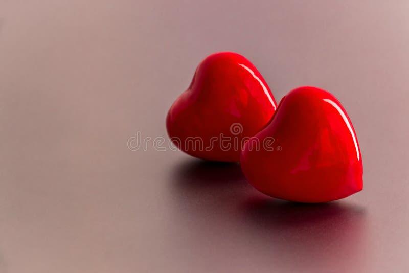Deux coeurs rouges brillants pour l'amour et le fond de valentines images libres de droits