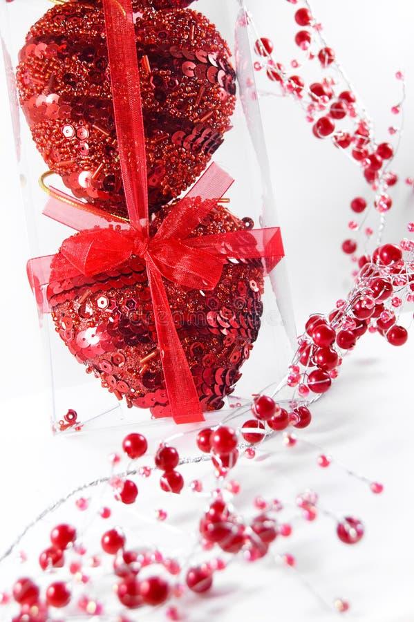 Deux coeurs rouges dans l'emballage et les programmes transparents photo stock