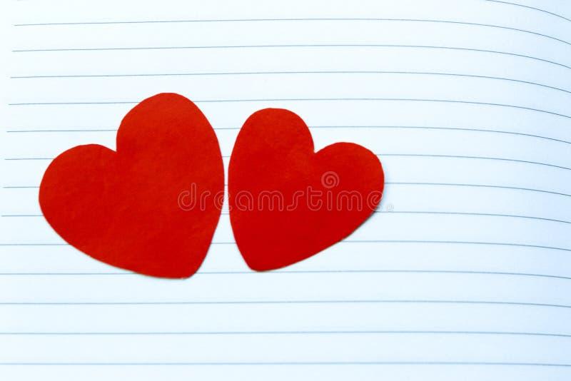 Deux coeurs rouges sur Notebook& x27 ; page de s photos stock