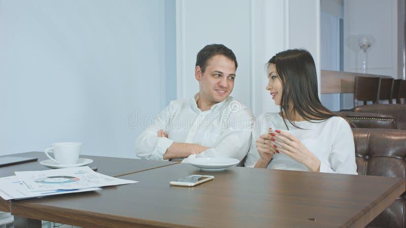 Deux collègues amicaux parlant et buvant du café dans un café photos stock