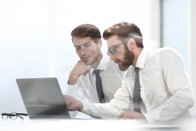 Deux collègues d'affaires discutent la documentation en ligne photographie stock