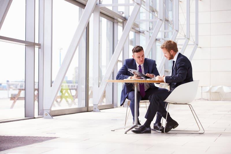 Deux collègues d'affaires lors de la réunion dans l'intérieur moderne de bureau photo libre de droits