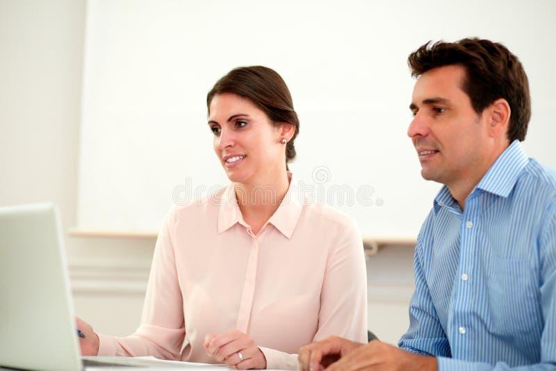 Deux collègues d'affaires regardant l'ordinateur portable photographie stock libre de droits