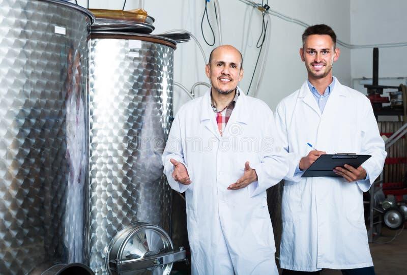 Deux collègues d'hommes dans des manteaux blancs fonctionnant dans la section de fermentation image stock