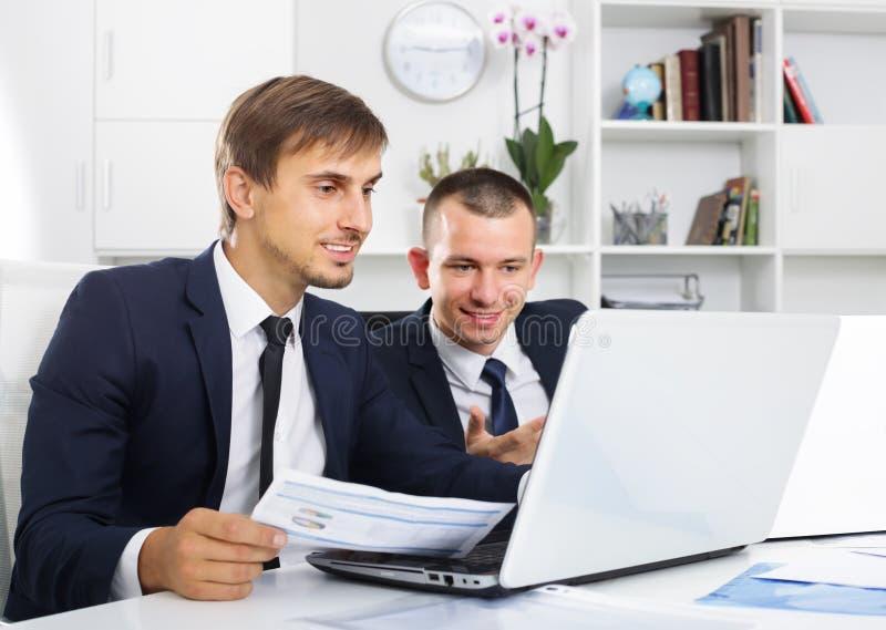 Deux collègues d'hommes travaillant sur des ordinateurs dans le bureau ferme images libres de droits