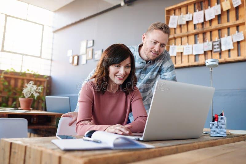 Deux collègues de sourire à l'aide d'un ordinateur portable ensemble dans un bureau photo libre de droits