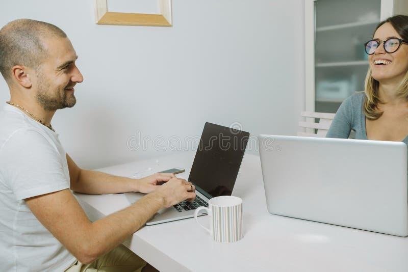 Deux collègues de sourire travaillant sur l'ordinateur portable ensemble au bureau photos libres de droits