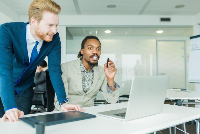 Deux collègues discutant des défauts de conception de graphiques dans un blanc gentil photos stock
