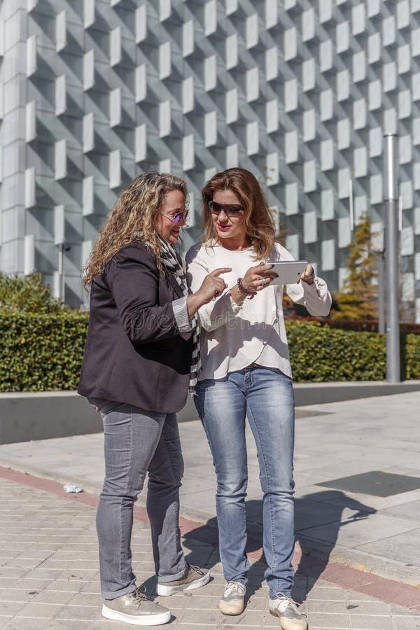 Deux collègues féminins au travail discuter quelque chose importante devant un immeuble de bureaux images stock