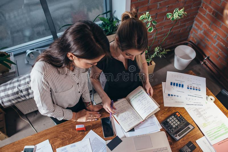 Deux collègues féminins dans le bureau fonctionnant ensemble photographie stock