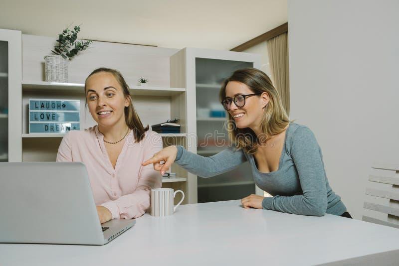 Deux collègues féminins discutent un projet avec l'ordinateur portable dans l'offic images libres de droits