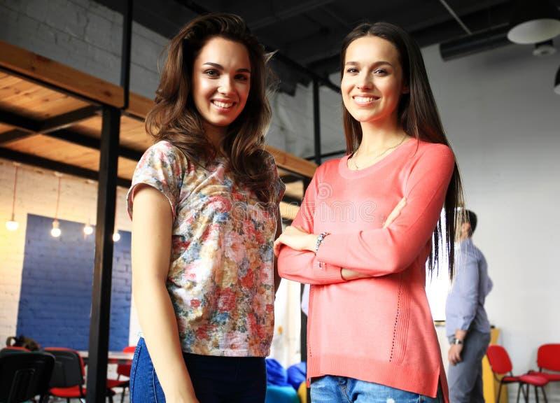 Deux collègues féminins se tenant l'un à côté de l'autre dans le bureau photos stock