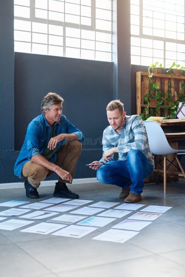 Deux collègues parlant ensemble au-dessus des écritures sur un plancher de bureau photos stock