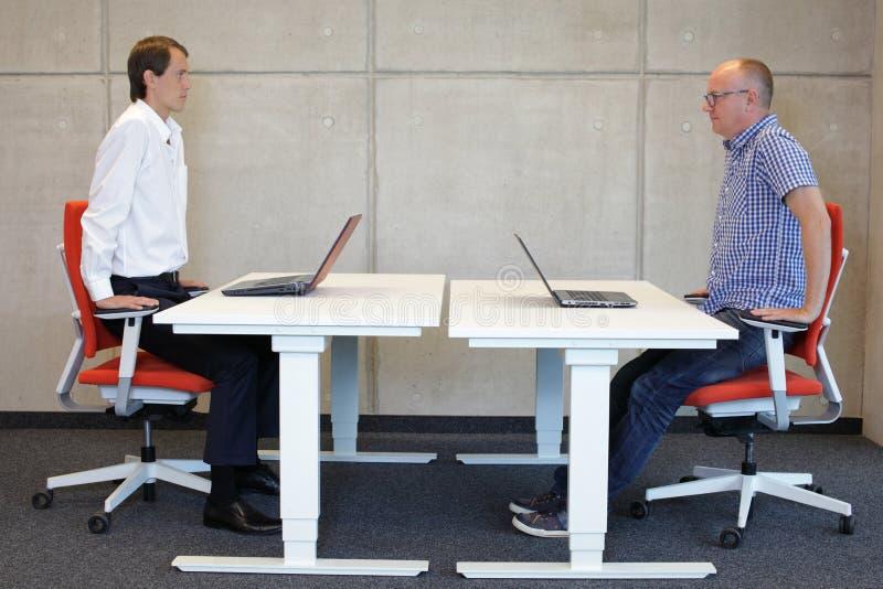 Deux collègues s'exerçant sur des fauteuils aux postes de travail dans le bureau images stock