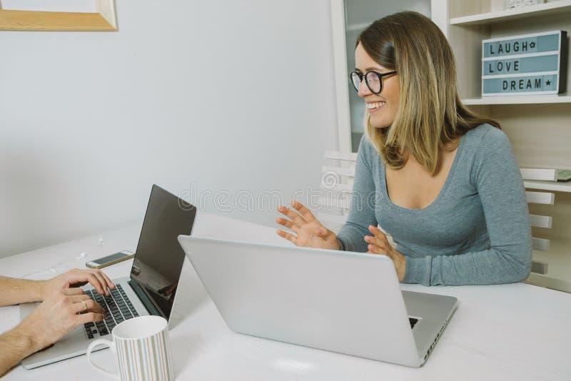 Deux collègues travaillant sur l'ordinateur portable ensemble au bureau photographie stock libre de droits