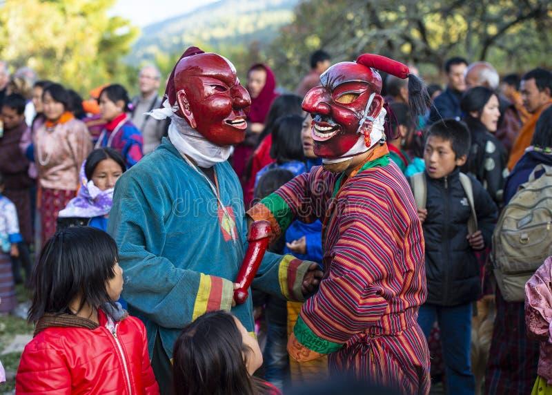 Deux comédiens chatouillent des citoyens pendant le jour de fête, Bhutan photographie stock libre de droits