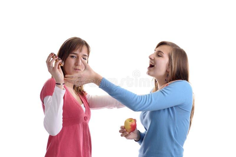 Deux combats de jeune femme pour un wafel images stock