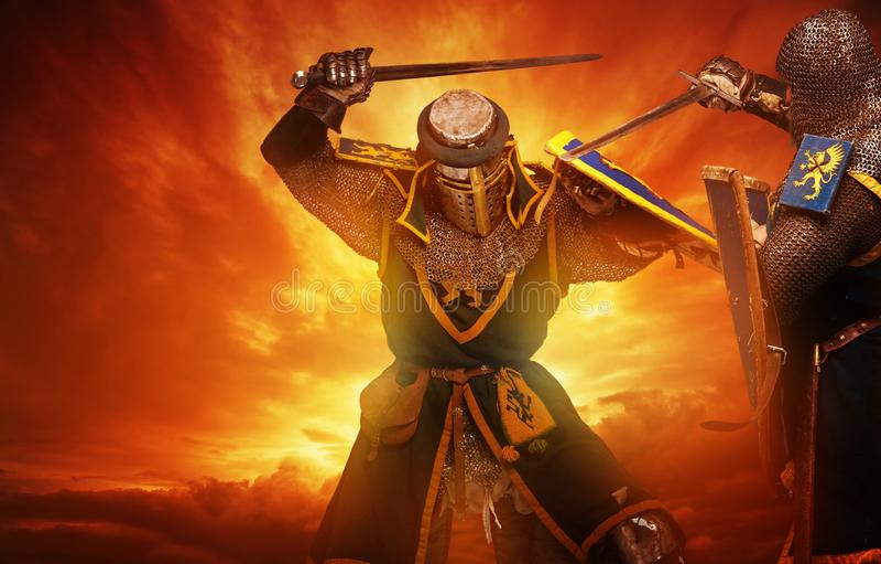 Deux combats médiévaux de chevaliers contre le ciel orageux photographie stock