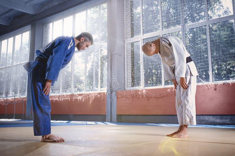 Deux combattants de judo se saluant dans un arc avant de pratiquer des arts martiaux dans un club de combat image stock
