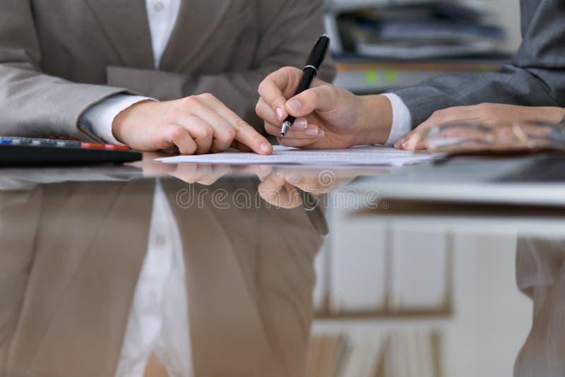 Deux comptables féminins comptant sur le revenu de calculatrice pour l'achèvement de feuille d'impôt, plan rapproché de mains Ser photo libre de droits