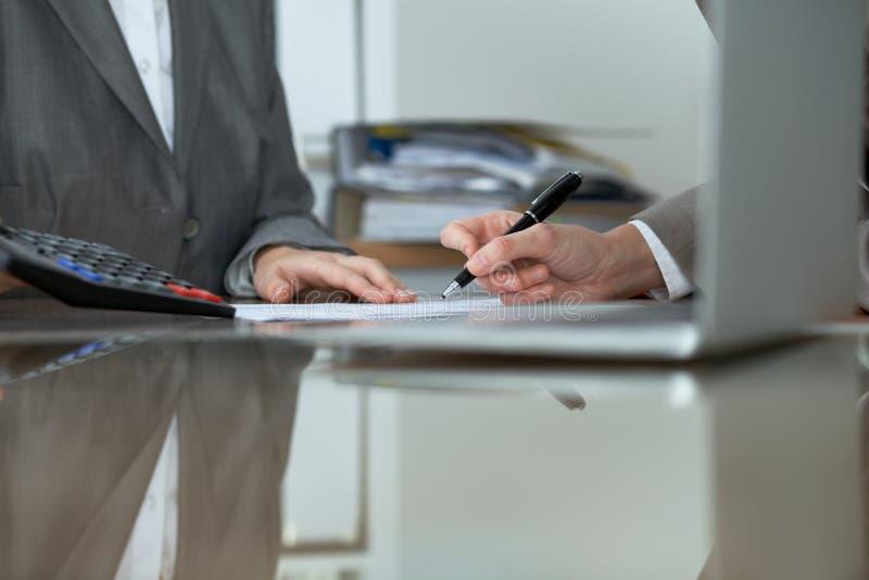 Deux comptables féminins vérifiant le relevé de compte financier ou comptant par le revenu de calculatrice pour la feuille d'impô images stock