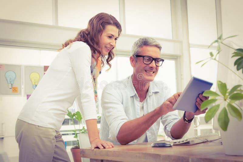 Deux concepteurs occasionnels de sourire travaillant avec le comprimé photos stock