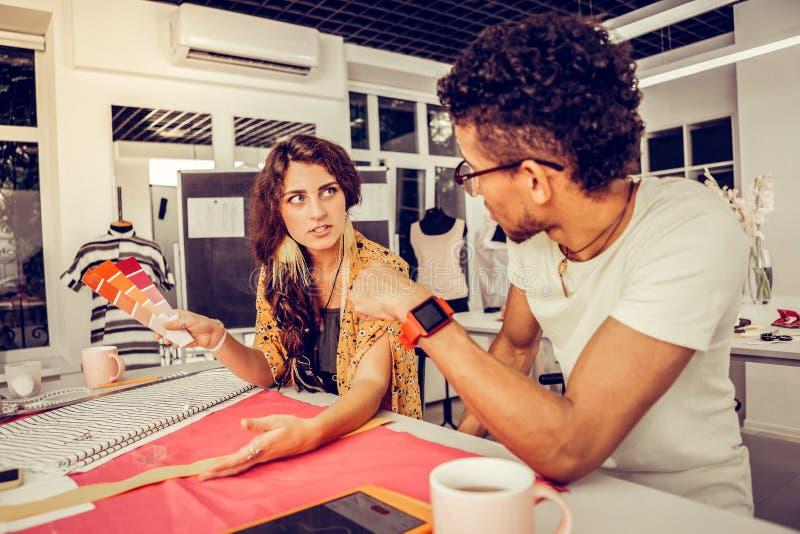 Deux concepteurs sérieux discutant les échantillons de couleur images libres de droits