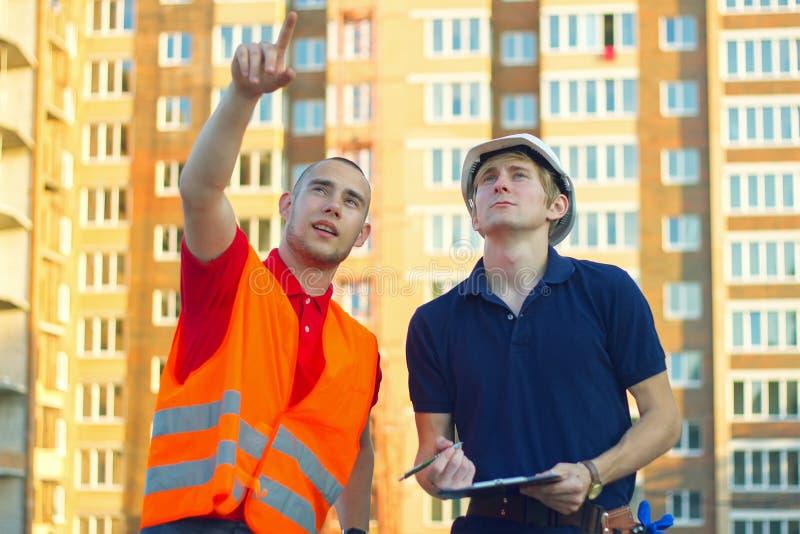 Deux constructeurs d'ingénieur avec le modèle prévoient au chantier de construction photos stock