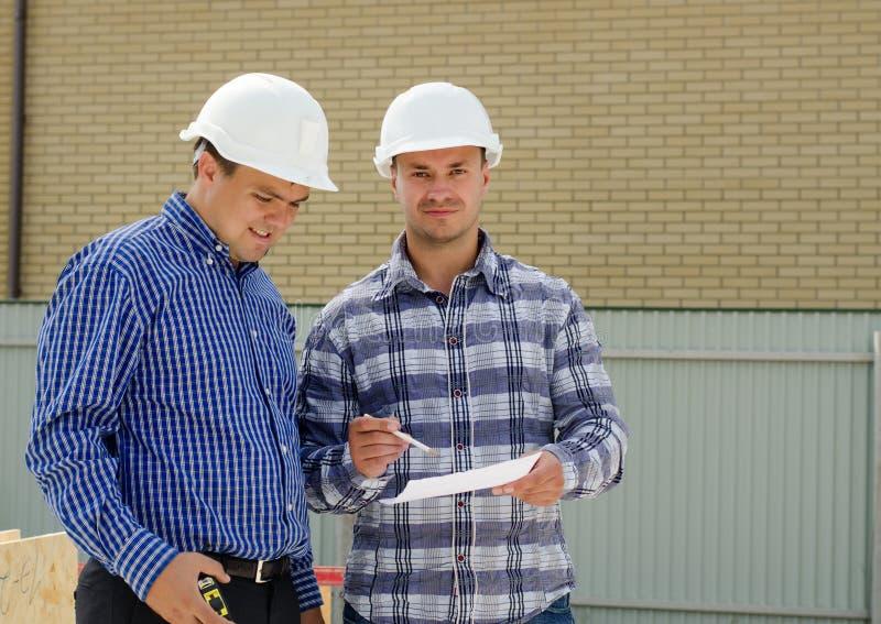 Deux constructeurs ou ingénieurs discutant des écritures photo stock