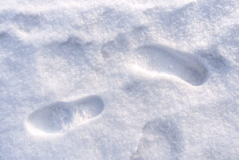 Deux copies de chaussures de pied humain sur la neige fraîchement tombée blanche photo stock