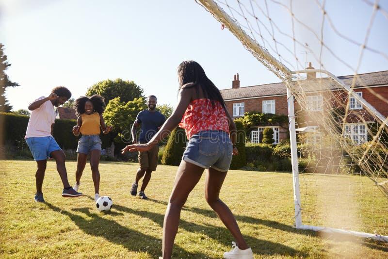 Deux couples adultes noirs jouant au football dans le jardin photo libre de droits