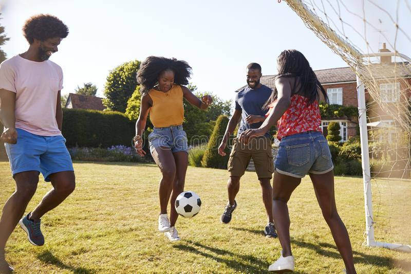 Deux couples adultes noirs jouant au football dans le jardin image libre de droits