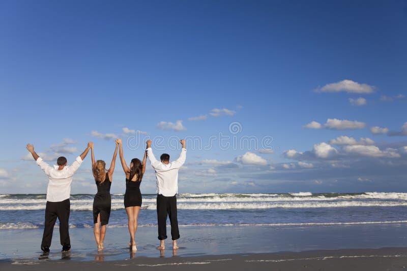 Deux couples, bras célébrant vers le haut sur la plage photos libres de droits
