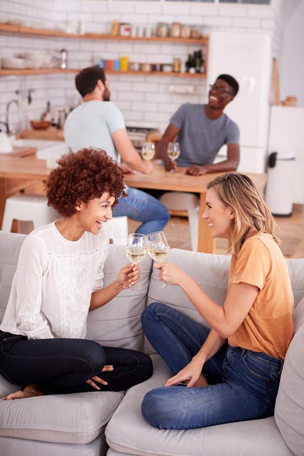 Deux couples détendant sur Sofa At Home With Glass de vin parlant ensemble photos stock