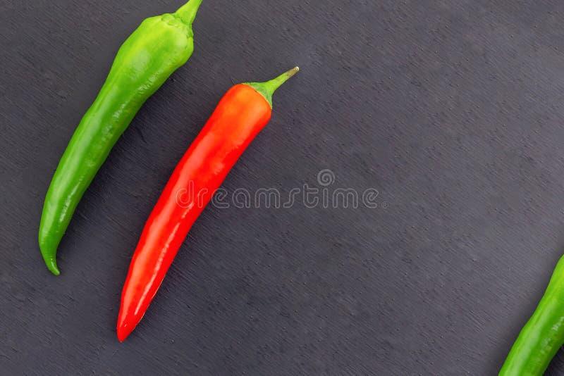 Deux couples de légumes des cosses minces de piments poivrent le cadre vert rouge de pièce de piment sur un espace noir de copie  image stock