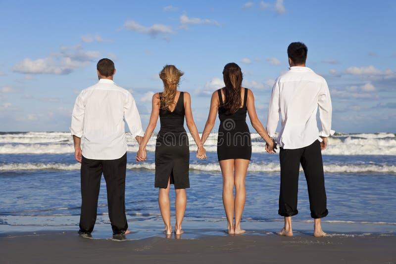 Deux couples, retenant des mains sur une plage image stock