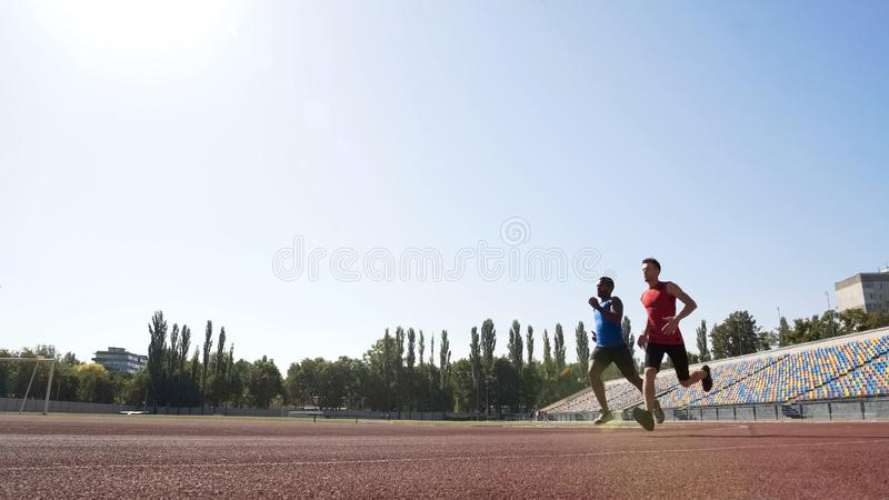 Deux coureurs actifs concurrençant au stade, s'exerçant dur pour réaliser le succès de sport images stock
