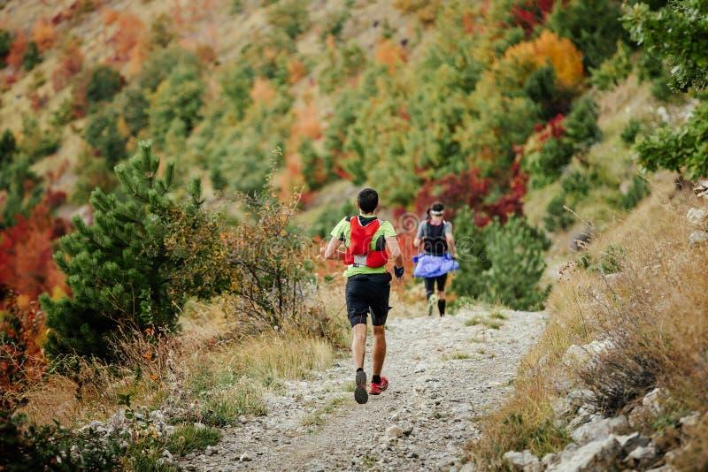 Deux coureurs courent un marathon de montagne images stock