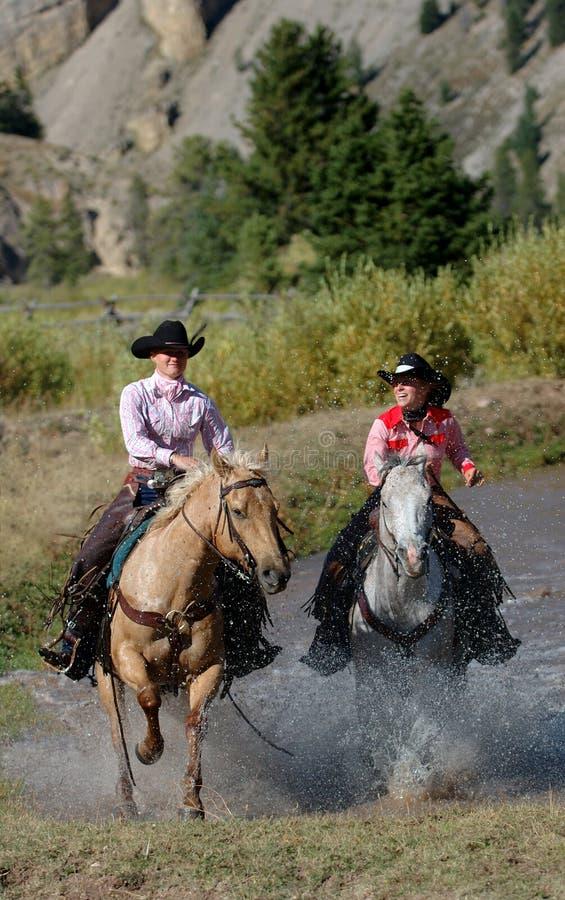 Deux cow-girls apparaissant de l'étang images stock