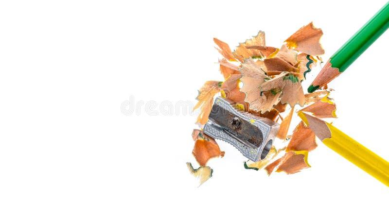 Deux crayons de couleur, affûteuses en métal et copeaux en bois de crayon photographie stock libre de droits